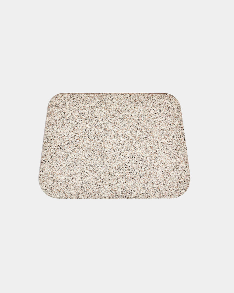 Rounded corner speckled beige rubber desk mat on white background.
