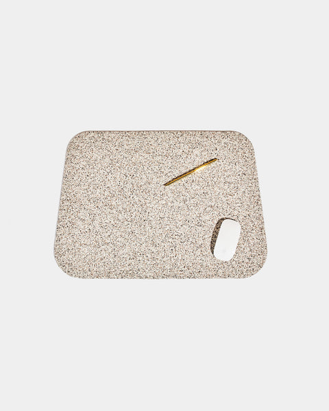 Rounded corner speckled beige rubber desk mat with brass pen and white mouse on white background.