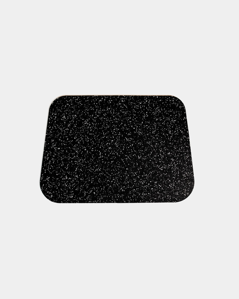 Rounded corner speckled black rubber desk mat on white background.