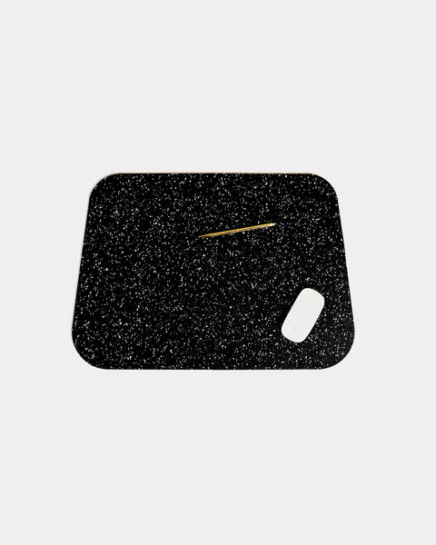 Rounded corner speckled black rubber desk mat with brass pen and white mouse on white background.