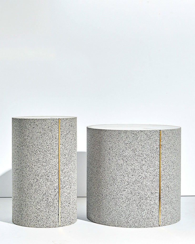 Two round side tables with speckled gray rubber, brass strip and concrete table top.