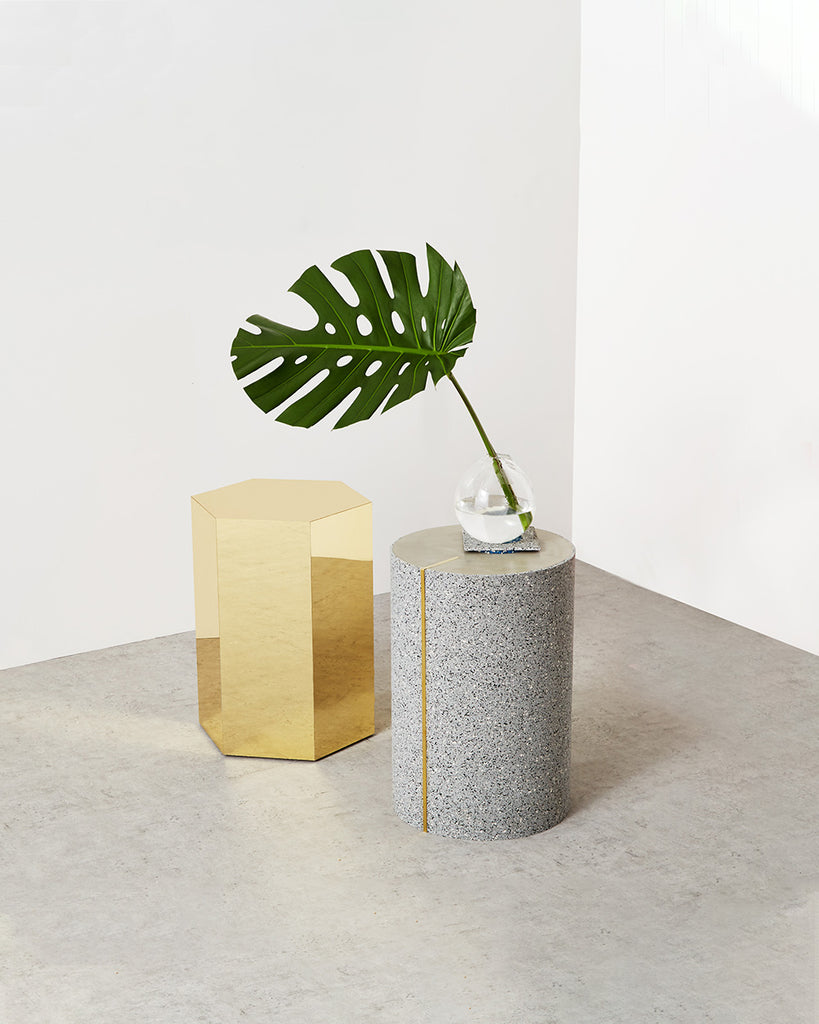 Round side table with speckled gray rubber, brass strip and concrete table top. Brass hexagon side table on concrete floor.