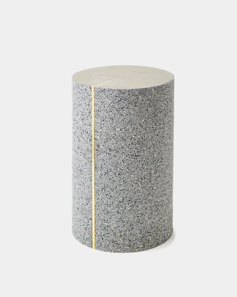 Round side table with speckled gray rubber, brass strip and concrete table top.