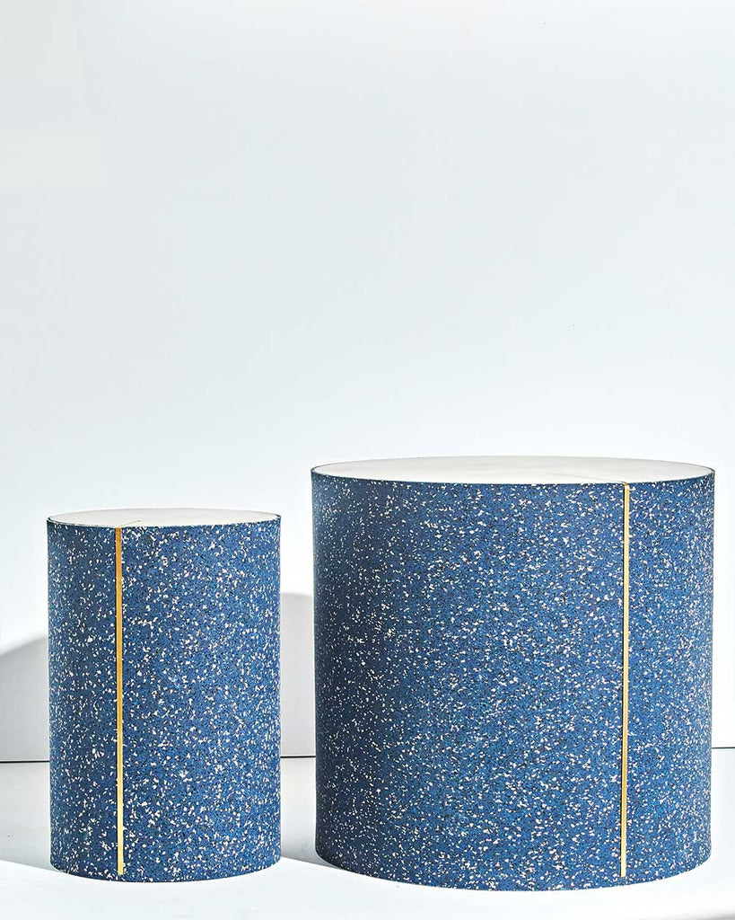 Two round side tables with speckled blue rubber, brass strip and concrete table top.