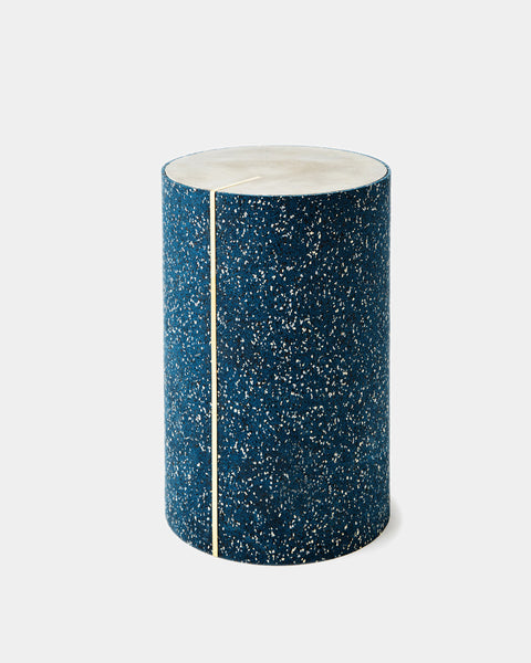 Round side table with speckled blue rubber, brass strip and concrete table top.