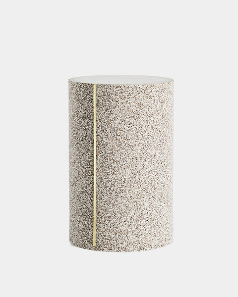 Round side table with speckled beige rubber, brass strip and concrete table top.