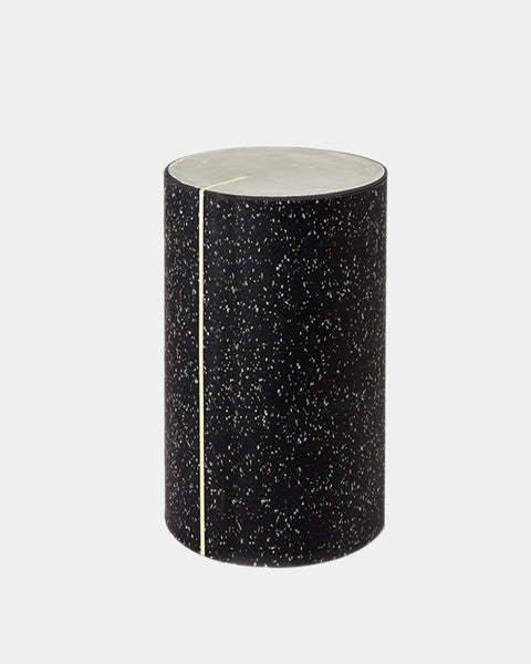 Round side table with speckled black rubber, brass strip and concrete table top.