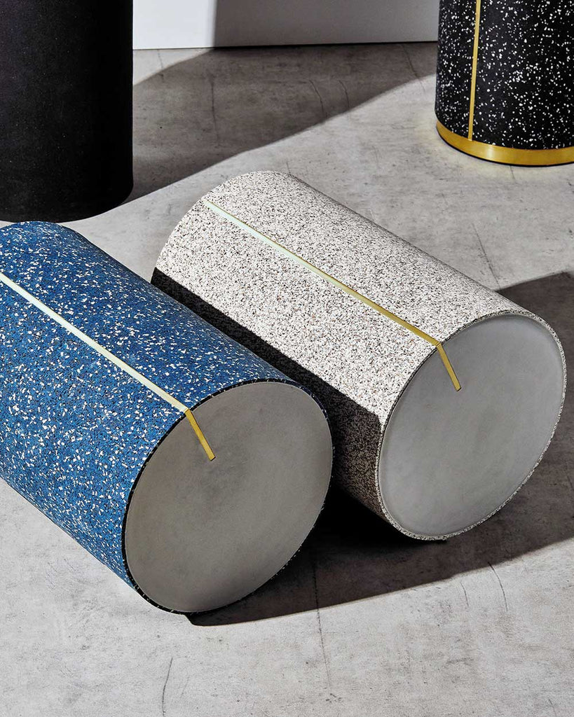 Round speckled blue and speckled beige rubber side tables with brass strip and concrete table top laid down on concrete floor