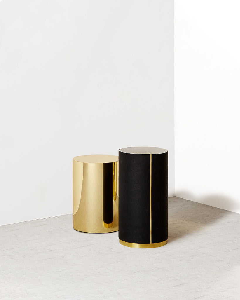 One round brass side table. One round black rubber side table with brass strip, brass trim and gray concrete table top.