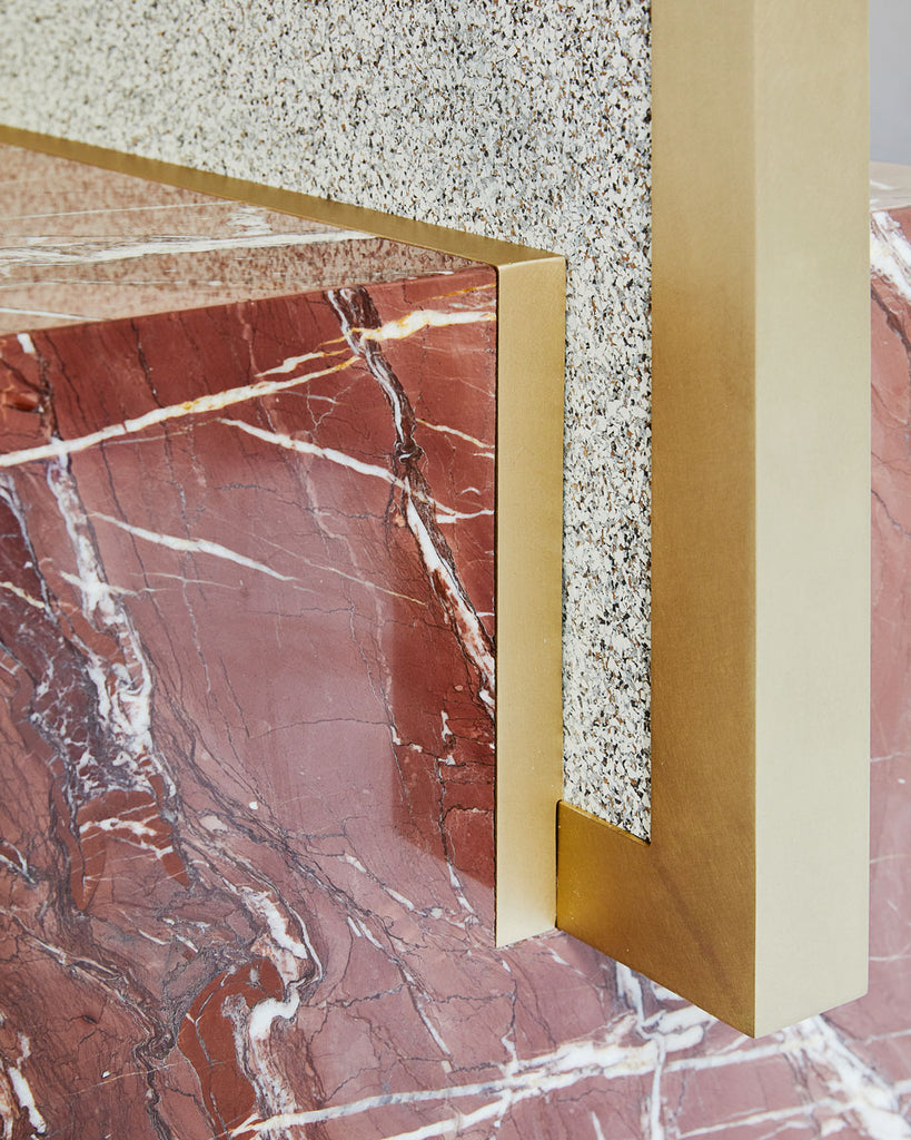 Cube base detail image of standing mirror with red jasper marble base and brass mirror frame, speckled beige rubber back.