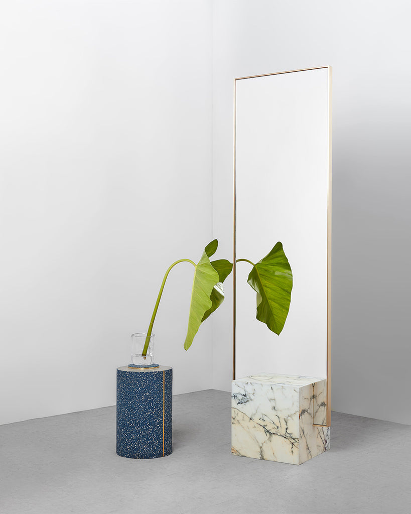 Standing mirror with white marble base and brass mirror frame. Next to the mirror is round, speckled blue rubber side table.
