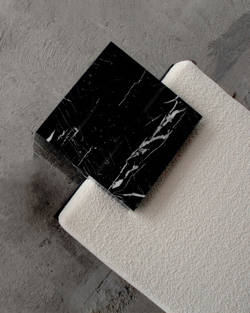 Detail image of bench showing cube nero marquina marble base, blackened steel structure and beige boucle fabric upholstered mattress.