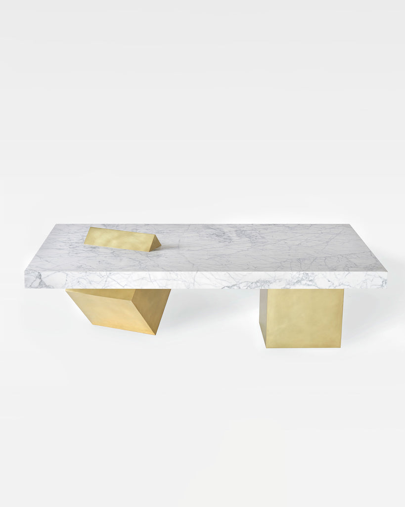 Coffee table with rectangular white carrara marble top and two cube brass legs. One of the brass cube leg is standing on its knife-edge slicing through marble top.
