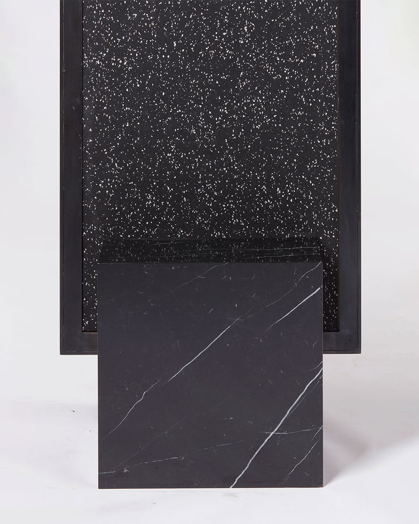 Cube base detail image of standing mirror with nero marquina marble base and blackened steel mirror frame, speckled black rubber back.