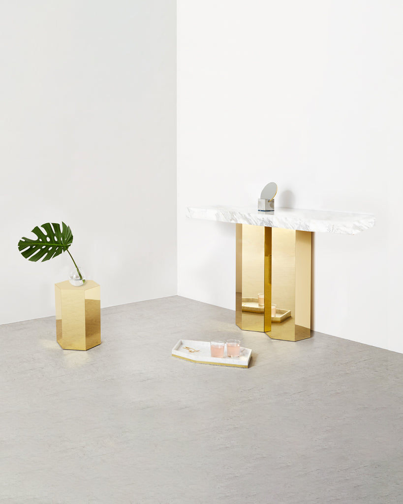 Console with white marble top and two brass hexagon legs, brass hexagon side table and marble tray on concrete floor.