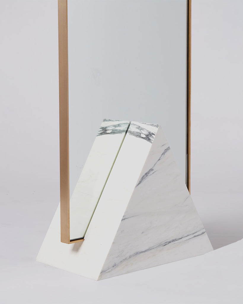 Triangular base detail image of standing mirror with white marble  base and brass mirror frame.