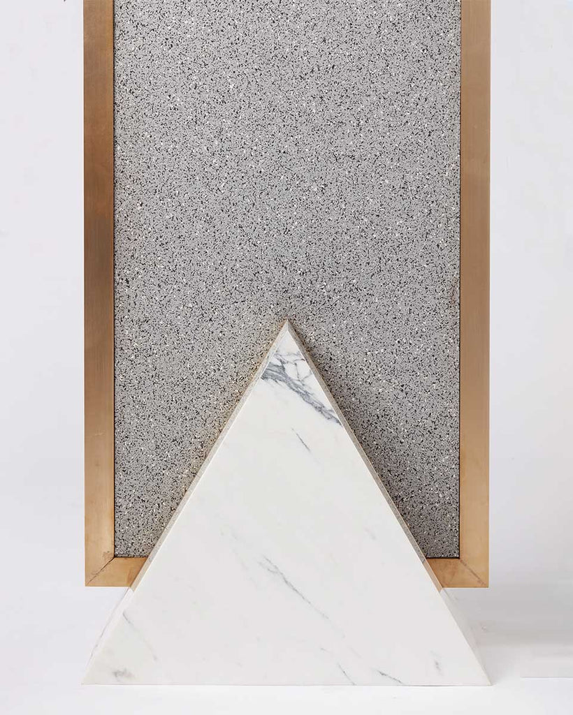 Triangular base detail image of standing mirror with white marble base and brass mirror frame, speckled grey rubber back.