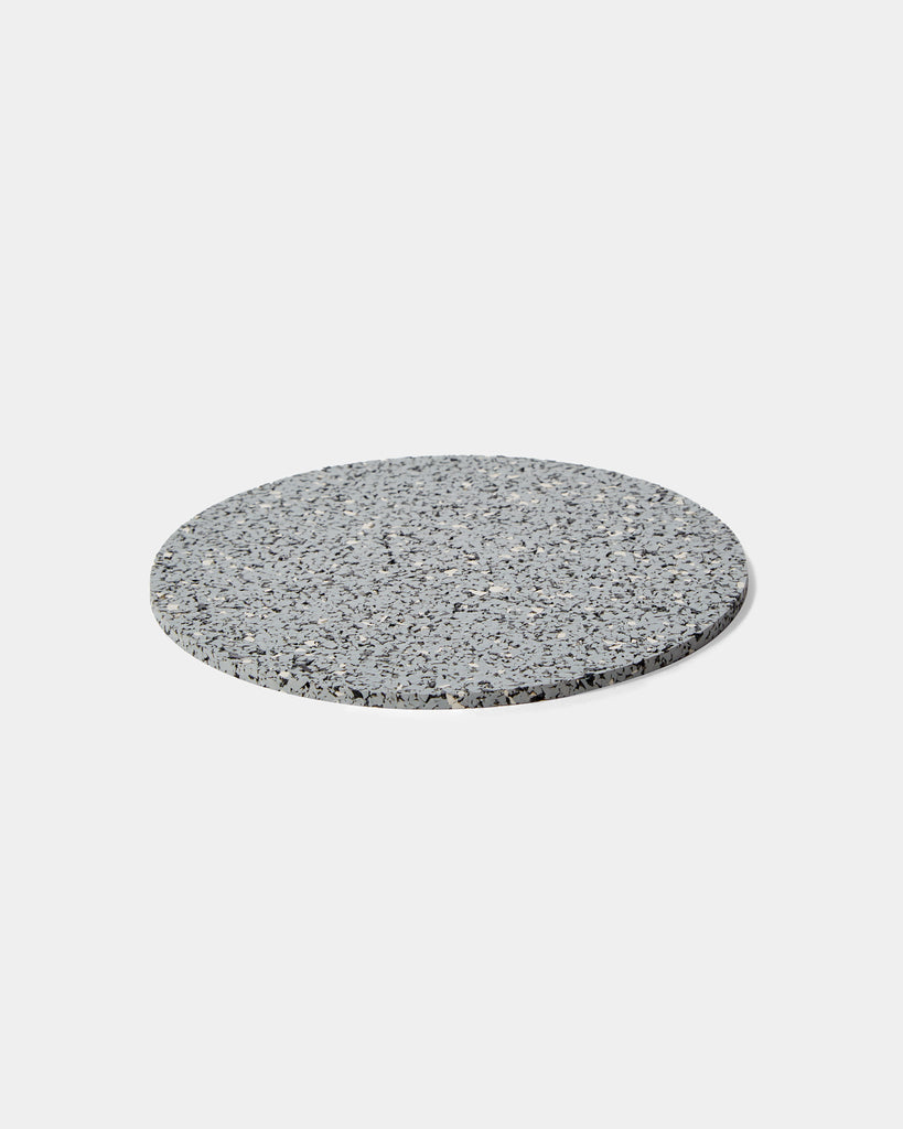 Round speckled grey rubber trivet on white surface.