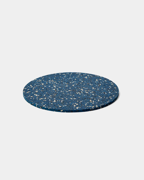 Round speckled blue rubber trivet on white surface.