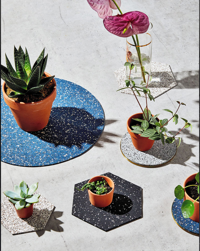 Round brass and rubber trivets and hexagon rubber trivet styled with small green plants on concrete surface.