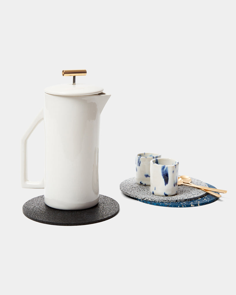 Round rubber trivets with white ceramic french press, two espresso cups and two brass spoons.