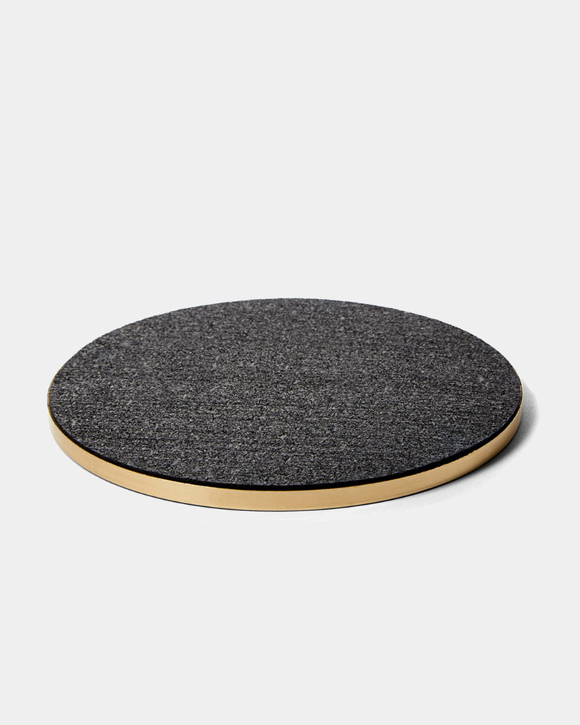 Round brass and black rubber trivet on white surface.