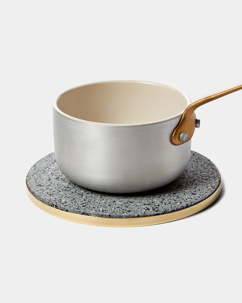 Round brass and speckled grey rubber trivet with silver small saucepan on white surface.