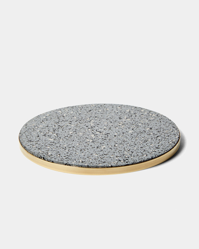 Round brass and speckled grey rubber trivet on white surface.