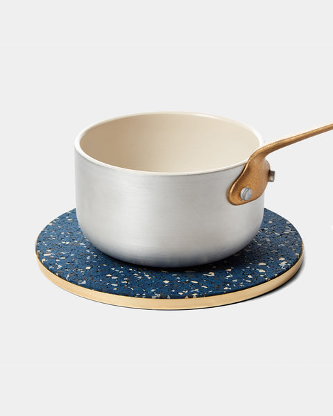 Round brass and speckled blue rubber trivet with silver small saucepan on white surface.