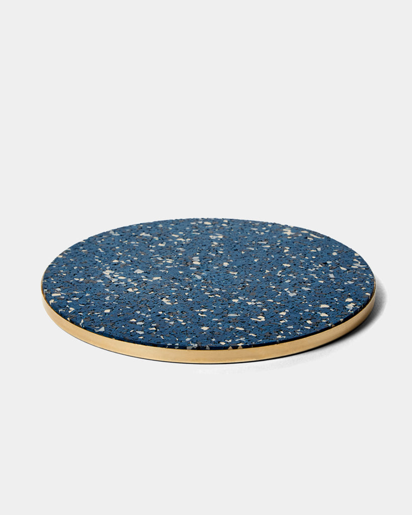 Round brass and speckled blue rubber trivet on white surface.