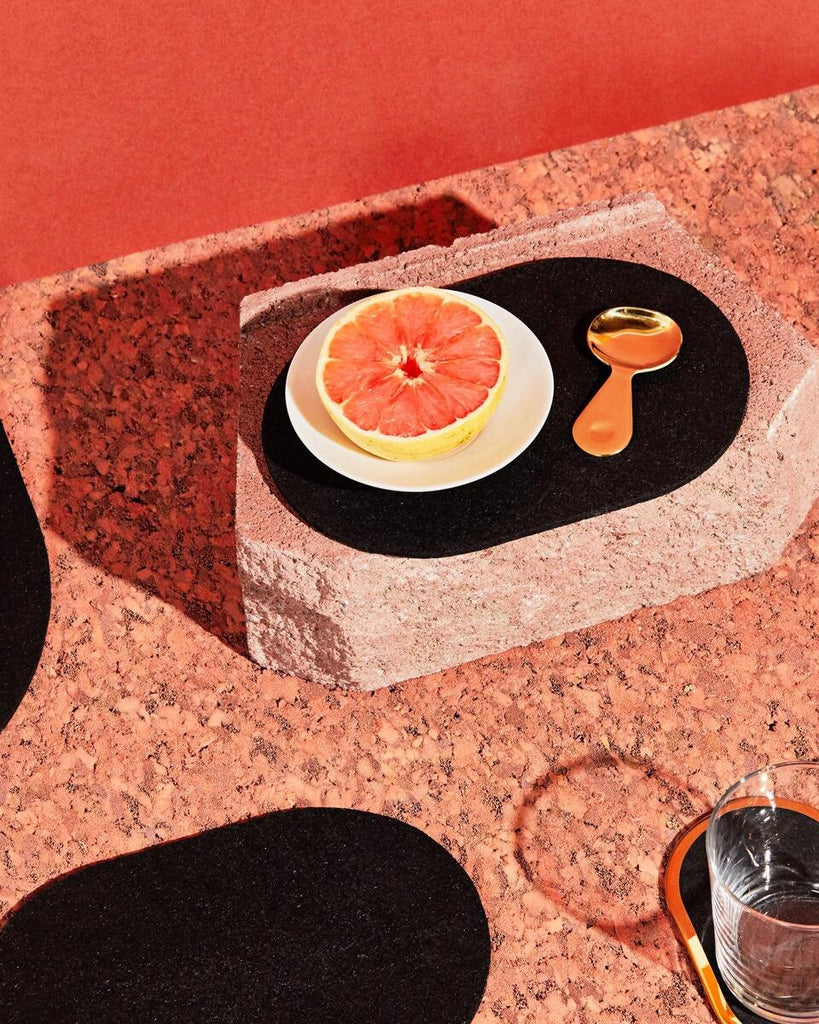 Black rubber capsule trivet placed on top of a brick on textured terracotta sienna surface. The trivet contains half a grapefruit on plate and a small brass spoon.