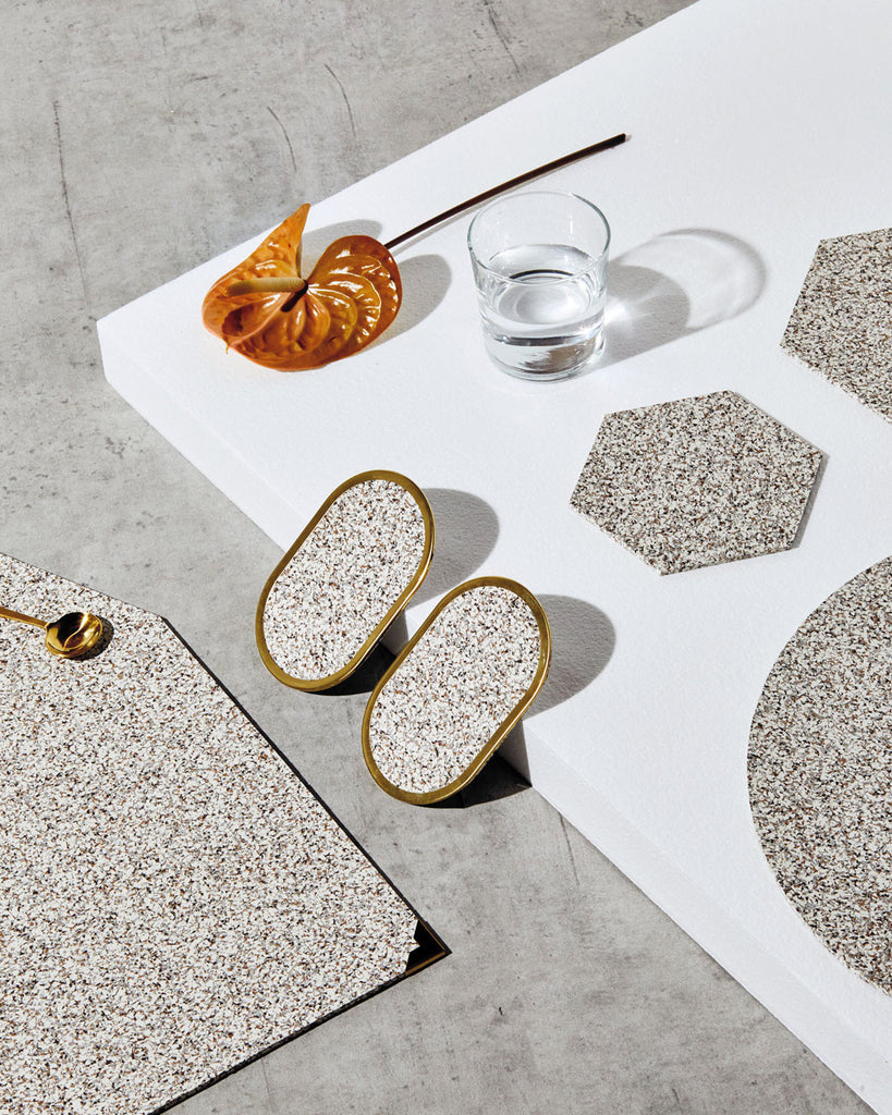Speckled beige rubber table setting with geometric placemats, hexagon trivets, and brass ring coasters styled with orange flower and glass of water.