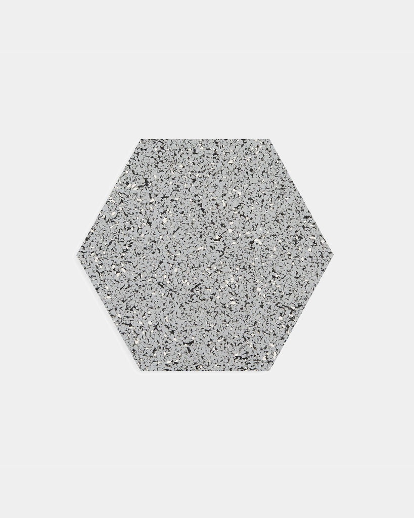 Hexagon speckled grey rubber trivet on white surface.