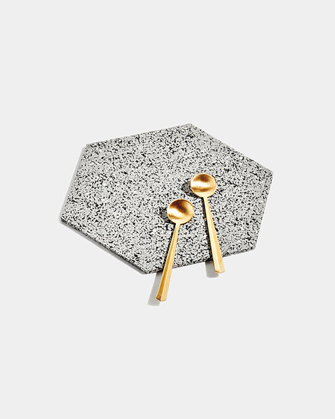Hexagon speckled grey rubber trivet with two brass tea spoons on white surface