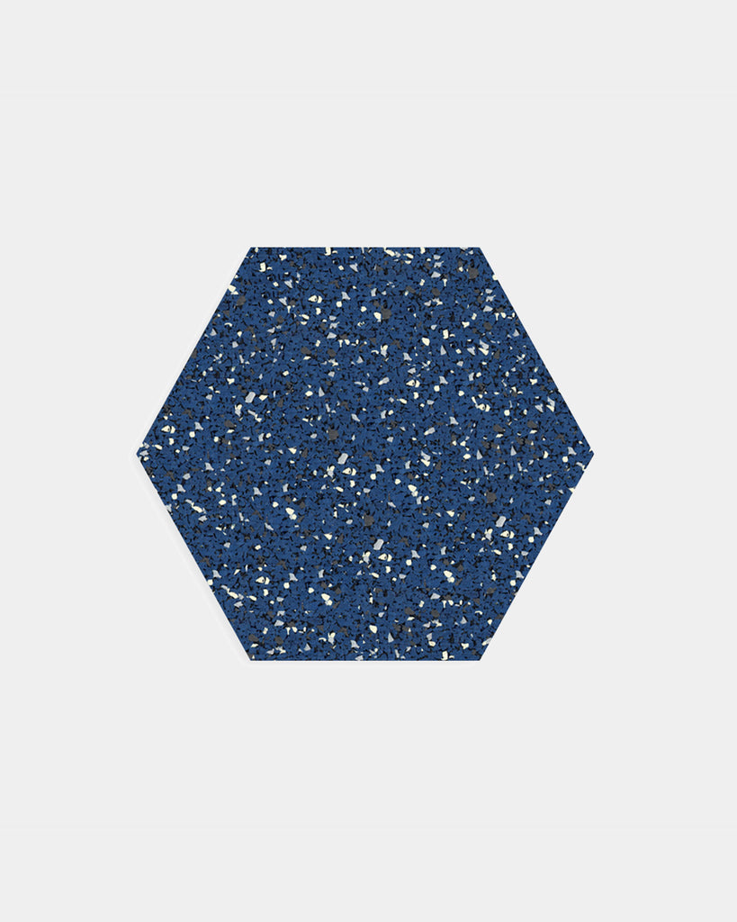 Hexagon speckled blue rubber trivet on white surface.