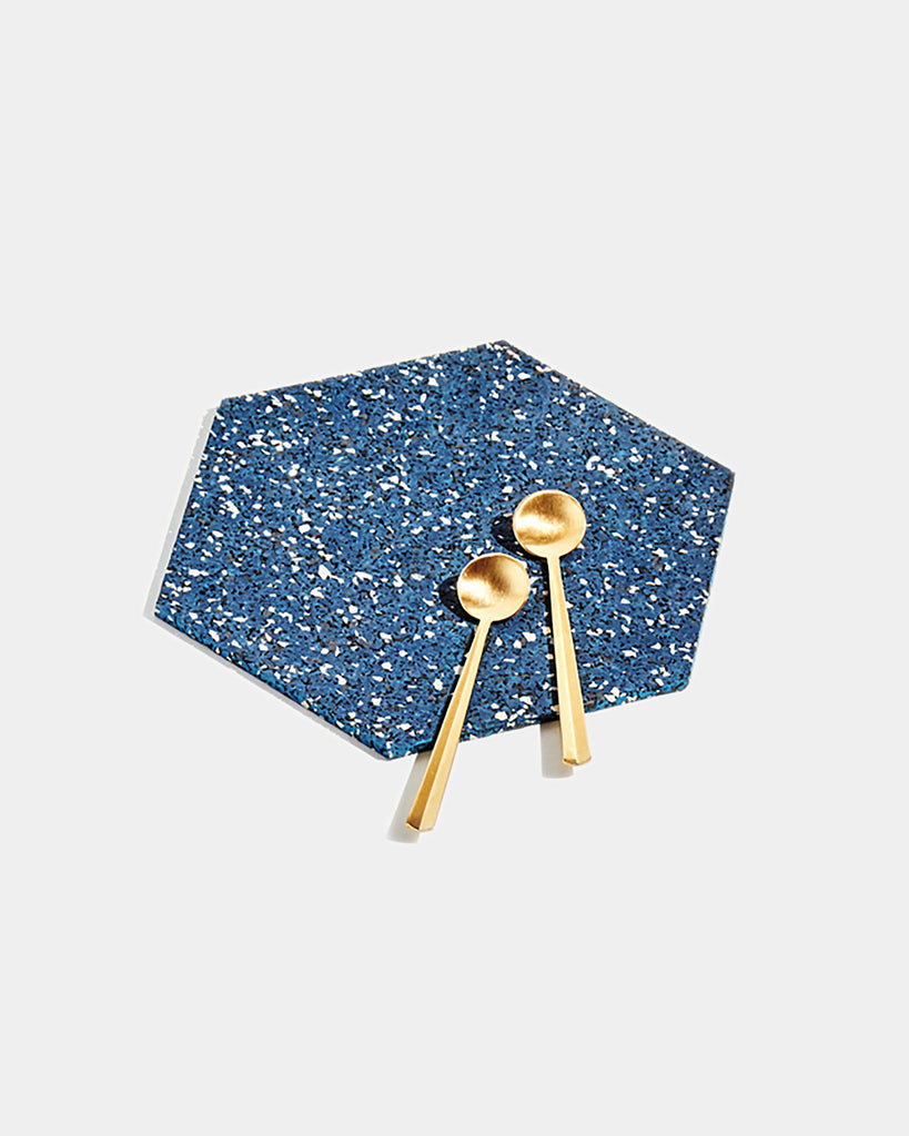 Hexagon speckled blue rubber trivet with two brass tea spoons on white surface.