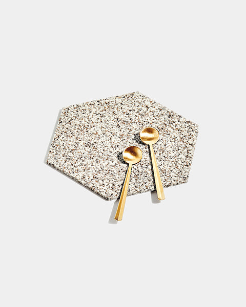 Hexagon speckled beige rubber trivet with two brass tea spoons on white surface