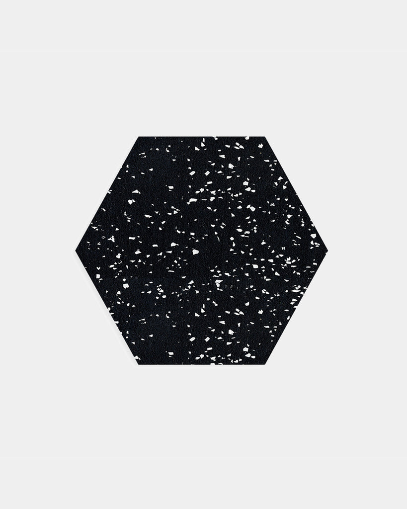 Hexagon speckled black rubber trivet on white surface.