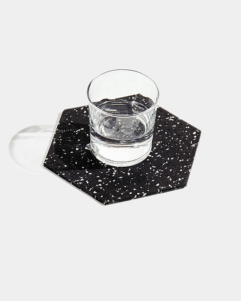 Hexagon speckled black rubber trivet with glass filled with water on white surface.