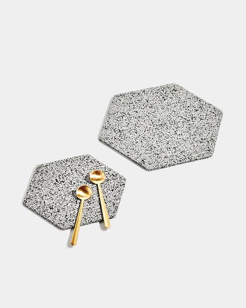 One small and one large hexagon speckled grey rubber trivet on white surface. Small trivet has two brass tea spoons placed on its surface.