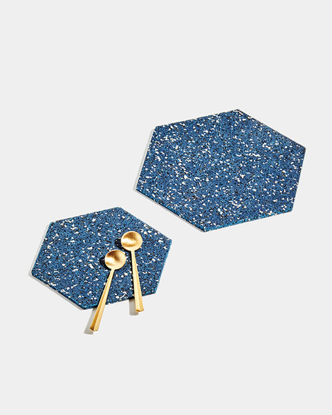 One small and one large hexagon speckled blue rubber trivet on white surface. Small trivet has two brass tea spoons placed on its surface.