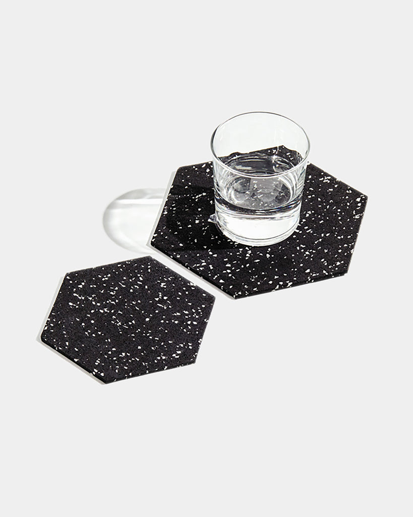 One small and one large hexagon speckled black rubber trivet on white surface. Large trivet has glass filled with water.