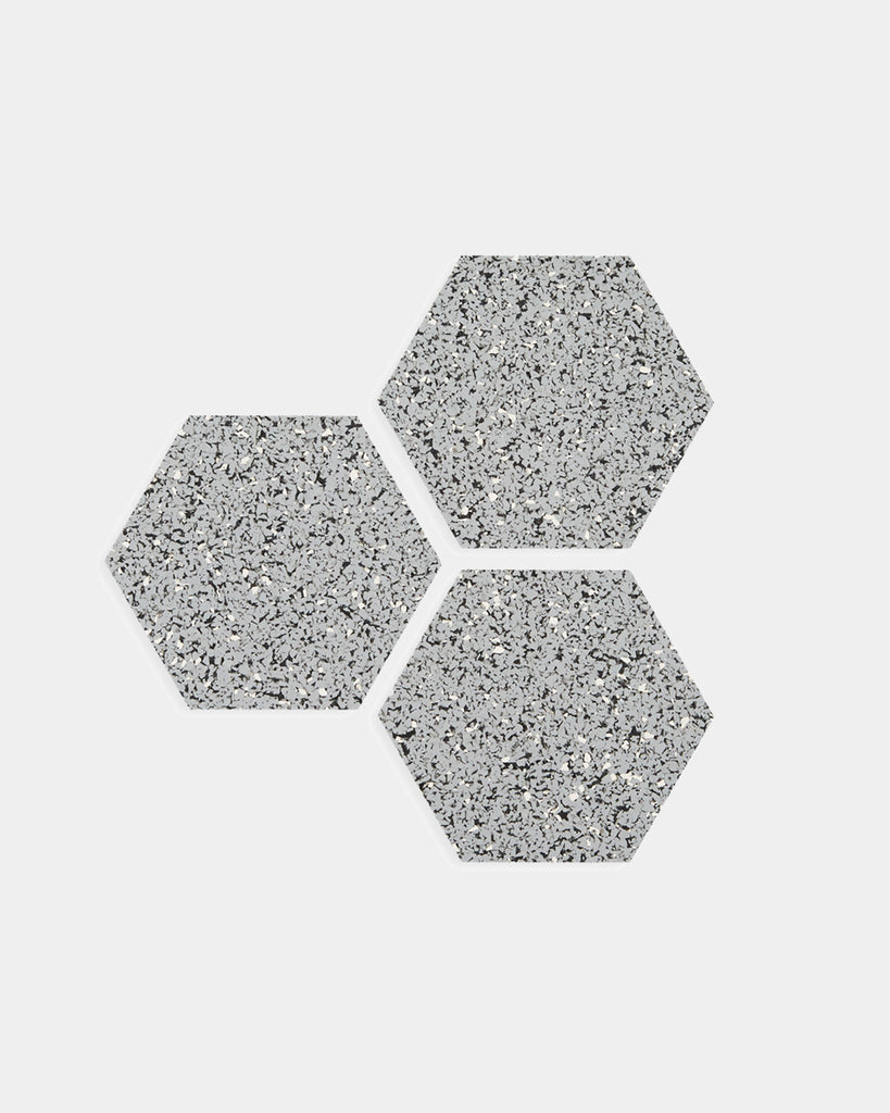 Three hexagon speckled grey rubber trivets on white surface.
