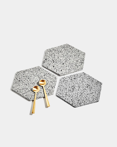 Three hexagon speckled grey rubber trivets on white surface. One trivet has two brass tea spoons.