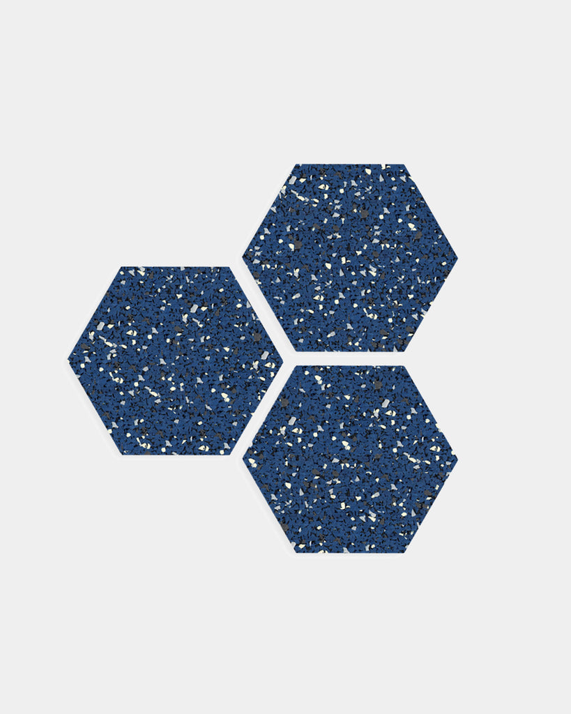 Three hexagon speckled blue rubber trivets on white surface.