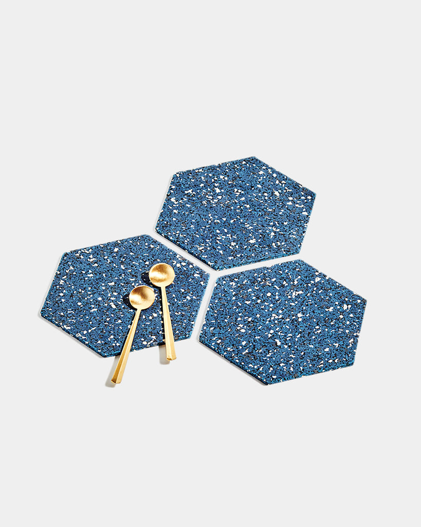 Three hexagon speckled blue rubber trivets on white surface. One trivet has two brass tea spoons.