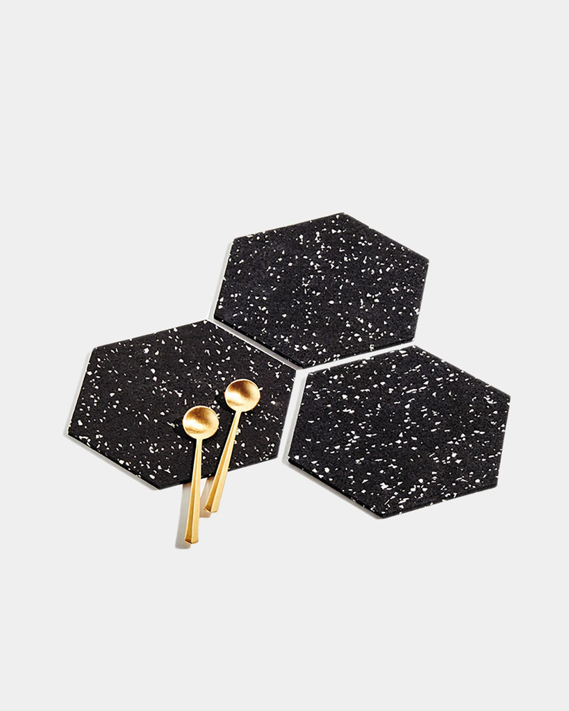 Three hexagon speckled black rubber trivets on white surface. One trivet has two brass tea spoons.
