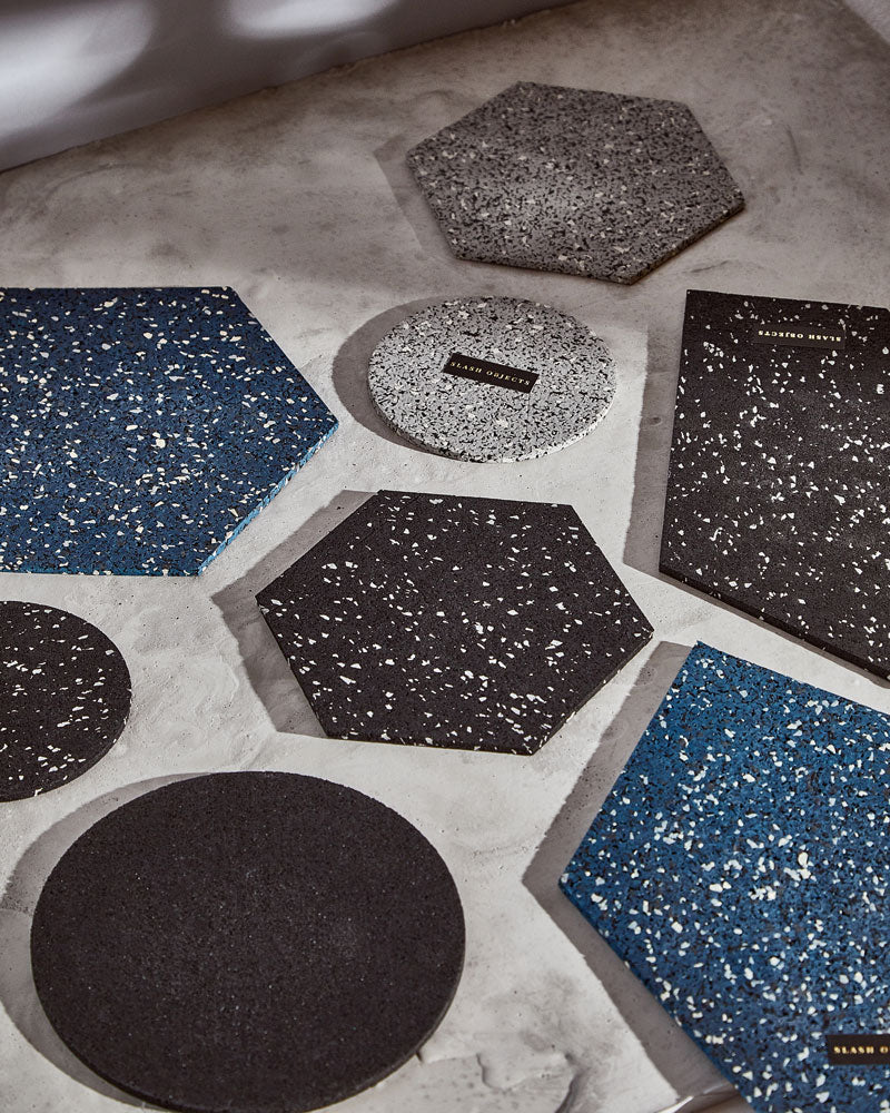 Round and hexagon rubber trivets on concrete surface.