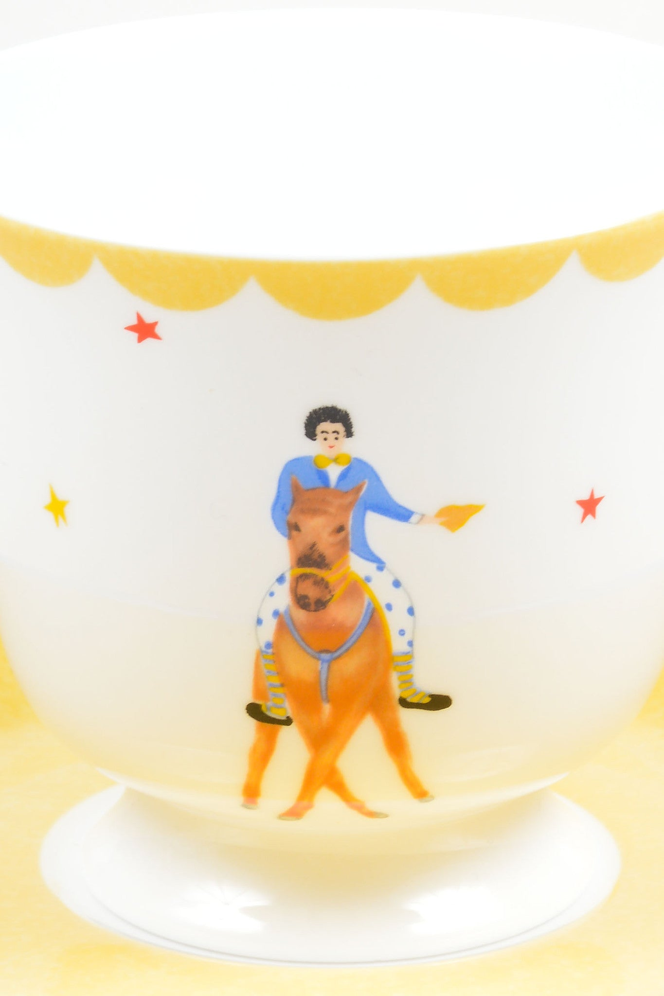 "White, Yellow and Blue Hermes Porcelain ""Le Clown Cavalier"" Circus Teacup and Saucer Front 2"