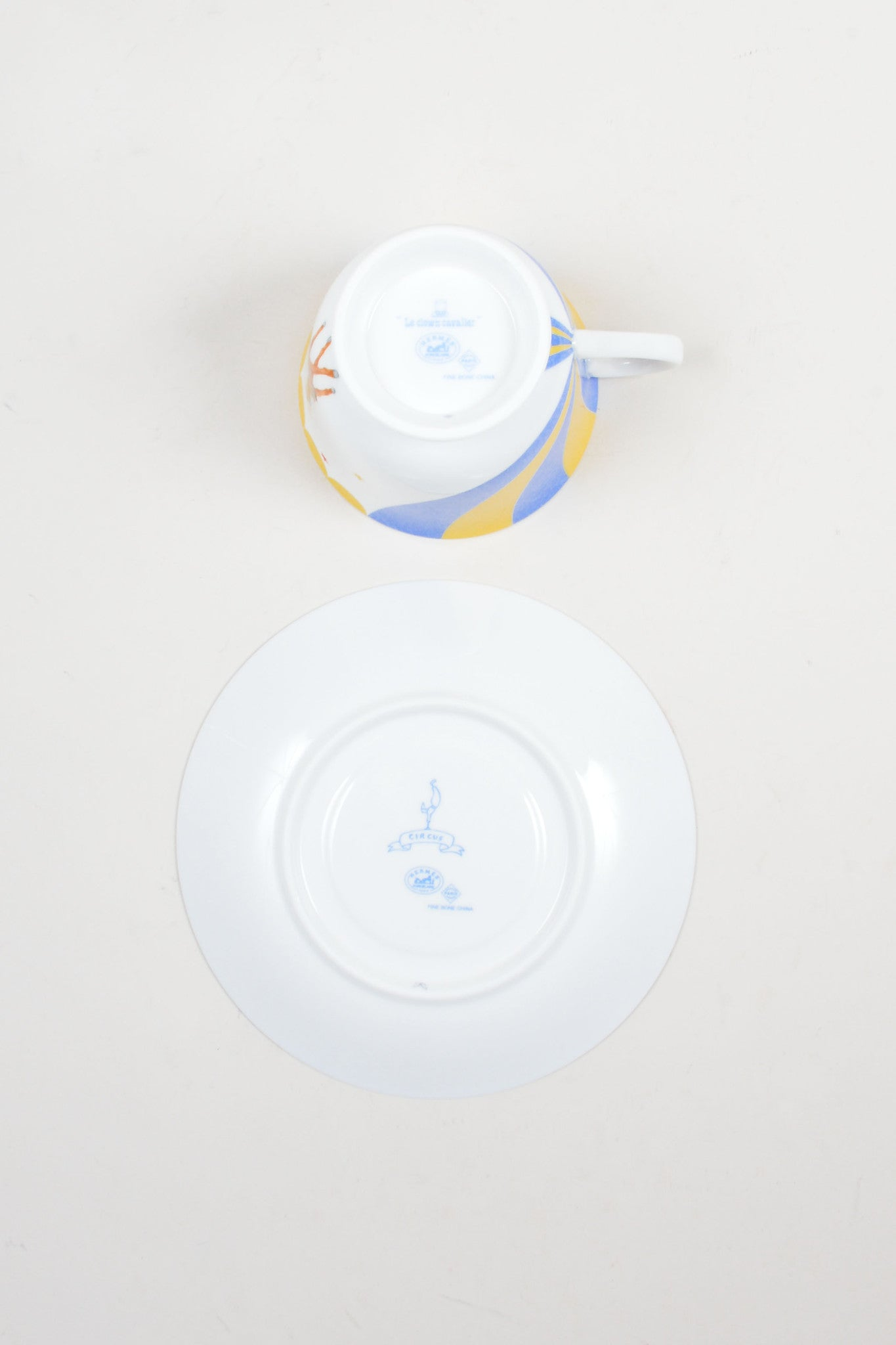 "White, Yellow and Blue Hermes Porcelain ""Le Clown Cavalier"" Circus Teacup and Saucer Bottom"